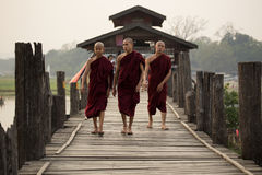Priests or monks walking on U Bein Bridge royalty free stock photos