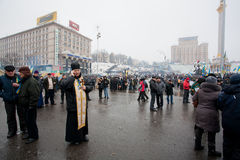 Priests talking on a cell phone outdoor. KIEV, UKRAINE: Catholic priests talking on a cell phone outdoor during anti-government Euromaidan protest. More than 800 Royalty Free Stock Photos