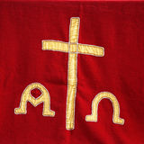 Priests vestment or church cloth. Decorative symbolic gold needlework on a priests vestment or church cloth with a gold cross and religious icons on a red Stock Photography