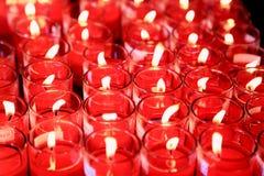Priez avec des lueurs d'une bougie rouges Images stock