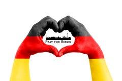 Priez pour Berlin, Allemagne, silhouette de ville à l'intérieur des mains de l'homme sous forme de coeur avec le drapeau de l'All Images stock