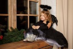 Priez une petite fille dans un costume noir d'ange, regardant avec espoir pour la paix Enfance et paix heureux Noël, an neuf Photographie stock