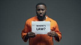Prigioniero afroamericano che tiene dove è il segno di legge in cellula, persona scorrettamente accusata video d archivio