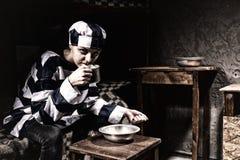 Prigioniero femminile arrabbiato che mangia dai piatti di alluminio in un piccolo pri fotografia stock