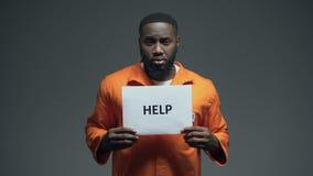 Prigioniero maschio afroamericano che tiene il segno di aiuto, chiedente la giustizia, abuso stock footage