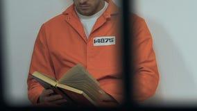 Prigioniero maschio caucasico che legge bibbia santa in cellula, speranza per perdono stock footage