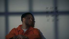 Prigioniero maschio che esamina le linee attraversate sulla parete cellulare, imprigionamento lungo servente stock footage