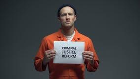 Prigioniero maschio che tiene il segno di riforma della giustizia penale, protezione di diritti umani video d archivio