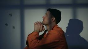 Prigioniero maschio innocente che prega chiedere la pietà e la libertà, girantesi verso il dio video d archivio