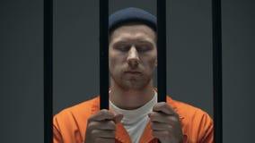 Prigioniero maschio nel fronte di chiusura di disperazione con le mani e pregare, sensibilità colpevole archivi video