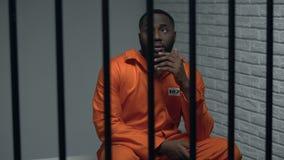 Prigioniero nero premuroso che si siede in cellula, protezione di diritti umani, imprigionamento archivi video