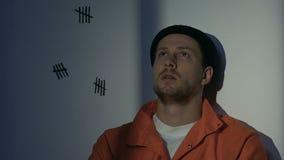 Prigioniero turbato che pensa alla vita sprecata in prigione, rammaricantesi circa il crimine fatto video d archivio