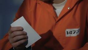 Prigioniero turbato in manette che tengono incrocio e che pregano a Dio, chiedente perdono archivi video