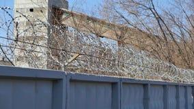 Prikkeldraad Egoza op de omheining op de achtergrond van een industriële faciliteit Stock Fotografie