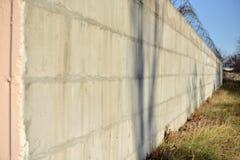 Prikkeldraad langs de baksteen geschilderde muren wordt uitgerekt die Stock Afbeelding