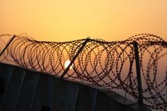 Prikkeldraad op de achtergrond van de zonsonderganghemel Stock Foto