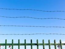 Prikkeldraad op omheining tegen blauwe hemel Symbool van unfreedom en ontbering Unfreedomconcept royalty-vrije stock foto's