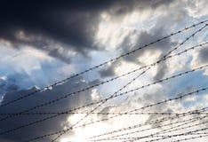 Prikkeldraad tegen de bewolkte hemelachtergrond Royalty-vrije Stock Fotografie