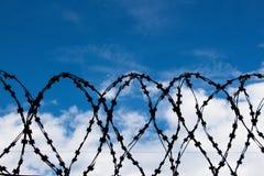 Prikkeldraad tegen de blauwe hemel Het symboliseert verbod of verantwoordelijkheid voor niet-vervulling van vereisten royalty-vrije stock afbeeldingen