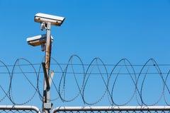 Prikkeldraadomheining met veiligheidscamera op blauwe hemel Stock Foto