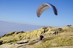 Paraglider tandem running on cliff to take off mountain summit royalty free stock images
