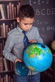 Primär skolpojke som studerar jordklotet Royaltyfria Bilder