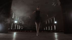 Prima ballerina on pointes training on stage with spotlights in late evening before important performance in Opera and