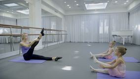 The prima ballerina teaches two children how to strench the leg in big bright gym. The traineer and girls sit on the mats and benting forward with knees stock video