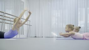 The prima ballerina teaches two girls to do back exersices from abdominal balance. The trainer and two little dancers lie on the mats on the floor and raise stock video footage