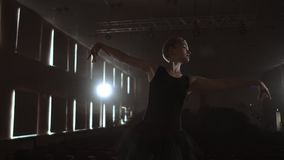 Prima ballet company in a dark dress on a dark theater stage rehearsing in the smoke performs dance moves in slow motion.  stock footage