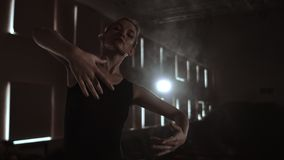 Prima ballet company in a dark dress on a dark theater stage rehearsing in the smoke performs dance moves in slow motion.  stock video footage
