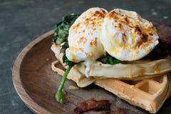 Prima colazione alta vicina con l'uovo affogato sulla cialda con spinaci e bacon sul piatto di legno di struttura sulla tavola di immagine stock libera da diritti