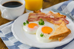 Prima colazione americana con sul piatto le uova, il bacon, il pane tostato, i pancake, il caffè ed il succo immagini stock libere da diritti