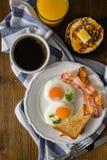 Prima colazione americana con sul piatto le uova, il bacon, il pane tostato, i pancake, il caffè ed il succo fotografie stock libere da diritti