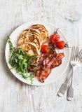 Prima colazione americana tradizionale - il bacon croccante, pancake con sciroppo d'acero, ha arrostito i pomodori, rucola Su un  fotografia stock libera da diritti