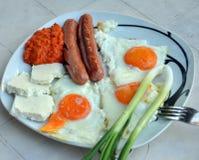 Prima colazione appetitosa con le uova fritte e le salsiccie fritte Fotografia Stock Libera da Diritti