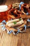 Prima colazione bavarese della salsiccia del vitello con le salsiccie, la ciambellina salata molle e fotografie stock libere da diritti
