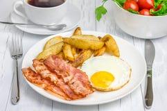 Prima colazione calorosa con bacon, uovo fritto, patata Fotografia Stock Libera da Diritti