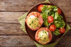 Prima colazione calorosa: uova affogate con il salmone e la salsa olandese Fotografie Stock