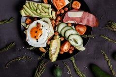 Prima colazione casalinga con il pomodoro affettato, bacon, pani, cetriolo, uovo, avocado, nocciola sul piatto fotografia stock