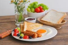 Prima colazione casalinga con sul piatto la salsiccia franco del pane tostato dell'uovo fritto Immagine Stock