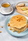 Prima colazione casalinga: i pancake stile americani sono servito con le bacche e il powderwith dello zucchero un la tazza di tè fotografia stock