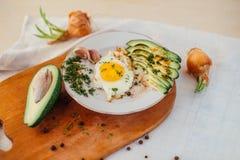 Prima colazione che consiste del pane tostato, uova, avocado, cipolle Immagine Stock