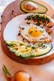 Prima colazione che consiste del pane tostato, uova, avocado, cipolle Fotografia Stock