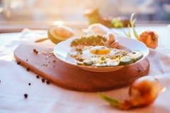 Prima colazione che consiste del pane tostato, uova, avocado, cipolle Immagini Stock