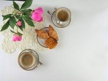 Prima colazione con due tazza di caffè e croissant, mazzo dei fiori rosa, vista superiore immagine stock