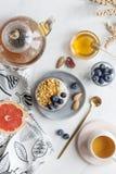 Prima colazione con granola, le bacche, il t? ed il pompelmo fotografia stock libera da diritti