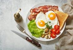 Prima colazione con il piatto delle uova fritte, del bacon, dei funghi e del pane tostato immagini stock libere da diritti
