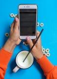 Prima colazione con latte e lo smartphone fotografie stock