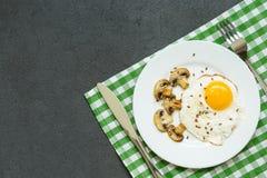 Prima colazione con le uova fritte, i funghi e le verdure in un piatto bianco su fondo scuro, vista superiore immagine stock libera da diritti